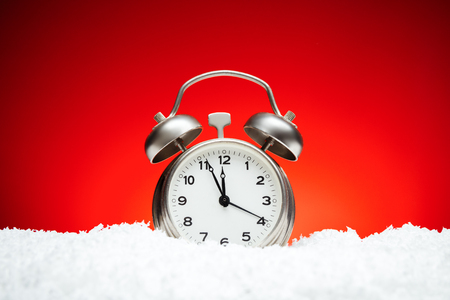 Christmas composition. Greeting card for new year clock Alarm clock on snow on red background with place for congratulatory text concept countdown to midnight holidays Stock Photo