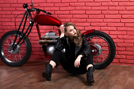 Coveted woman or girl in a leather jacket and tight pants, boots sits neer motorcycle, with an unusual hairdo and make-up on a brick red wall