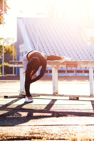 fitness girl on stadium, sporty women in sport suit, do exercises on sunny day. Sexy brunette with muscles body posing. female stretching near sports equipment