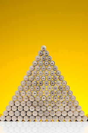 Ecology recycling concept, nature energy, used or new battery piramide, rechargeable AA accumulator, alkaline batteries in row on yellow background
