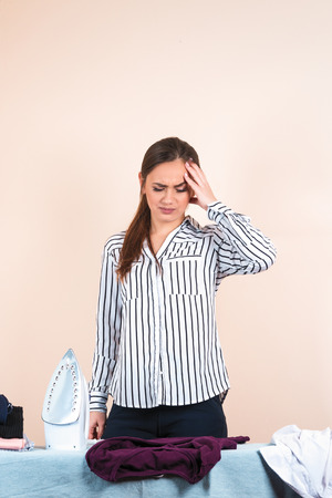 Young pretty woman in shirt ironing, housewife mother using iron on ironing board. Unhappy girl doing housekeeping on pastel background. Closeup portrait of attractive housewife with headache