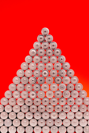 Ecology recycling concept, nature energy, used or new battery piramide, rechargeable AA accumulator, alkaline batteries in row on red background