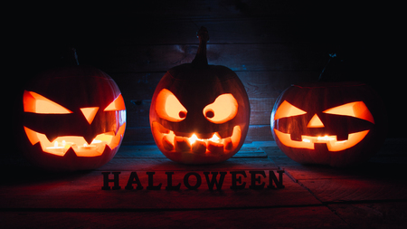 Halloween - pumpkins and candles in an abandoned wooden house on leaves and wooden boards with a warm and cold glow, against the background wooden floor top view with text halloween