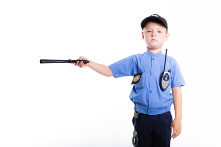 Cute little police boy with smile on face and baton on white background. Intelligent cool children in police suit with blue eyes and baton regulates traffic Banco de Imagens - 109807330