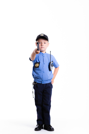 Cute little police boy with smile on face and baton on white background. Intelligent cool children in police suit with blue eyes and baton regulates traffic