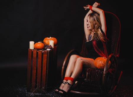 Halloween concept, girl vampire with red eyes red lips sit on rocking chair with pumpkins around. Scary crazy woman trick or treat time. Female makeup for holiday with jake lantern and taped hands Standard-Bild