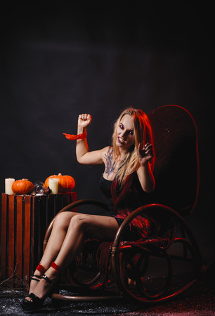 Halloween concept, girl vampire with red eyes red lips sit on rocking chair with pumpkins around. Scary crazy woman trick or treat time. Female makeup for holiday with jake lantern and taped hands 스톡 콘텐츠