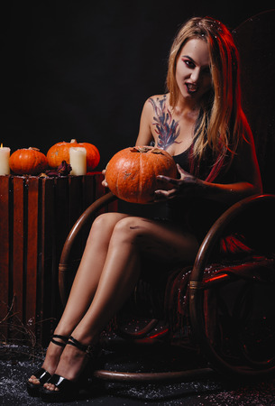 Halloween concept, girl vampire with red eyes red lips sit on rocking chair with pumpkins around. Scary woman trick or treat time, halloween composition. Female makeup for holiday with jake lantern 免版税图像