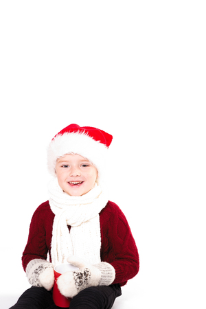 Merry Christmas and happy New year! Cute happy little boy holding red cup. Kid enjoy holiday santa hat. Portrait kid on light background isolated. Happy Child with place for text Banco de Imagens