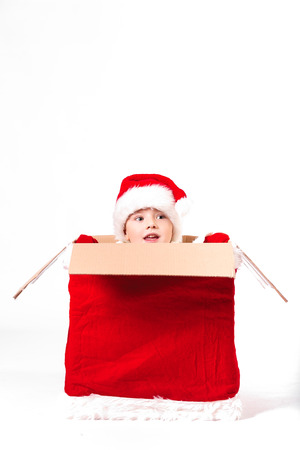 Merry Christmas and happy New year! Cute happy little boy sit in big christmas box with gift bag. Kid enjoy holiday in santa claus coat on light background. Happy Child with place for text.