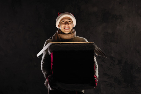 Christmas gift concept. Man in santa hat bring gift for you. Attractive man hold box.  Christmas and new year holiday celebration. Happy surprised man with opened his big present Stock Photo