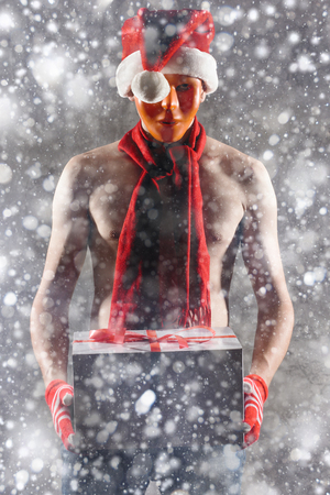 Christmas gift concept. Man in santa hat bring gift for you. Attractive man hold box.  Christmas and new year holiday celebration. Man in mask under snowflakes with nice torso wear hat, red scarf Stock Photo