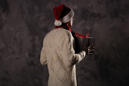 Christmas gift concept. Man in santa hat bring gift for you. Attractive man hold box.  Christmas and new year holiday celebration. Man look forward wear hat, red scarf, sweater Stock Photo - 112135304
