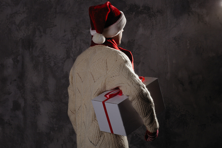 Christmas gift concept. Man in santa hat bring gift for you. Attractive man hold box.  Christmas and new year holiday celebration. Man look forward wear hat, red scarf, sweater
