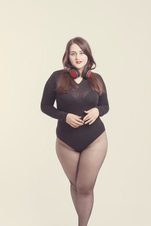 Model plus size with sweet donut, happy girl posing with headphones, in black bodysuit. XXL female on light background