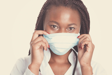 Female american african doctor, nurse woman wearing medical coat with stethoscope and mask. Happy excited for success medical worker posing on light background Stock Photo
