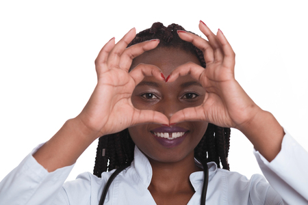 Female american african doctor, nurse woman wearing medical coat with stethoscope doing heart with hands and looking through it. Happy excited for success medical worker posing on light background isolated Foto de archivo