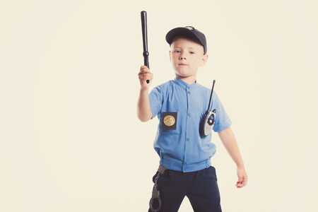 Cute little police boy with smile on face and baton on white background. Intelligent cool children in police suit with blue eyes and baton regulates traffic Banco de Imagens - 118468177