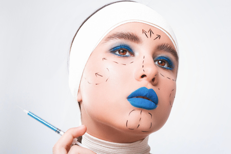 Beauty concept. Young model with blue lips and soft skin doing plastic surgery. Female with bandage on head, on light background. Girl want to do beautician injections with syringe.  Imagens
