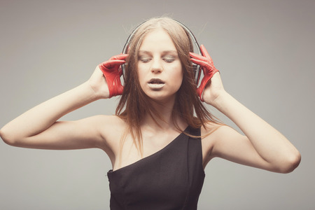 Fashion pretty girl listening music with headphones, wearing red gloves, close eyes and take pleasure with song