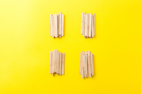 Few heap of many wooden ice cream sticks on yellow background. Concept gray crowd  and individual