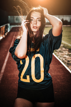 Sexy young sportive girls in t-shirt of rugby football player in action on the stadium. American football woman player stay on pitch with sunlight