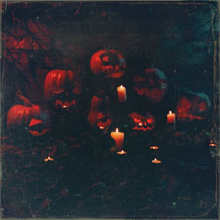 Concept of Halloween. many glowing orange and blue light angry terrible pumpkin, leaves, jack-lamp with candle of a happy Halloween, on a wooden background
