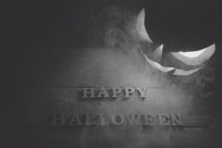 Halloween concept. Background of the holiday mystical pumpkin, jack lantern, in the dark with icy blue light and smoke with the letters Trick and Treat
