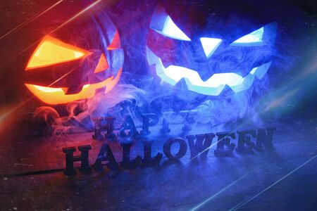 The concept of Halloween. two glowing oranjous and blue light angry scary pumpkin with smoke, jack-lantern, with happy Halloween inscription, on a wooden background Banco de Imagens