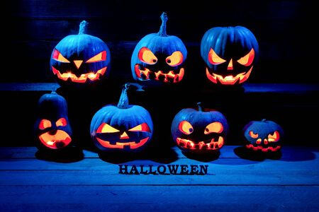 Halloween concept. Many Evil Scary Pumpkins in the dark with a blue ice glow. Jack Lantern with an inscription of halloween