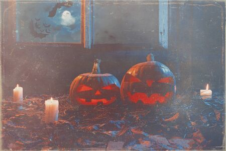 Halloween - pumpkins and candles in an abandoned wooden house on leaves and wooden boards with a warm and cold glow, against the background of a window with a mystic sky and bats, in a light smoke Banco de Imagens