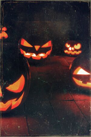 The concept of Halloween. Many glowing fiery light angry scary pumpkins. jack lantern in the dark, on a wooden background Banco de Imagens