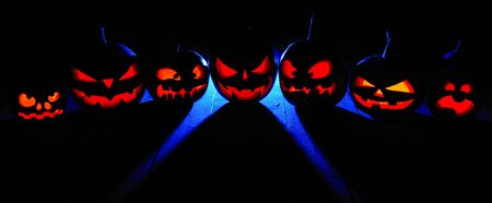 The concept of Halloween. Many glowing fiery light angry scary pumpkins. jack lantern in the dark, with a blue cool light behind on a wooden background Banco de Imagens