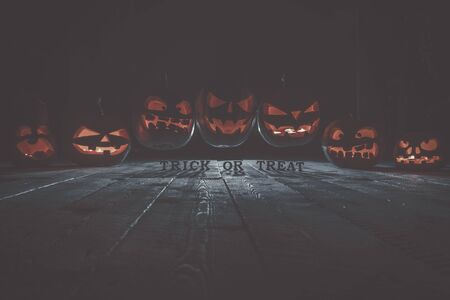 Concept of Halloween. Many glowing fiery light of evil scary pumpkins flying through the air. jack lantern, with the inscription trick or treat, with blue cool light behind on wooden background