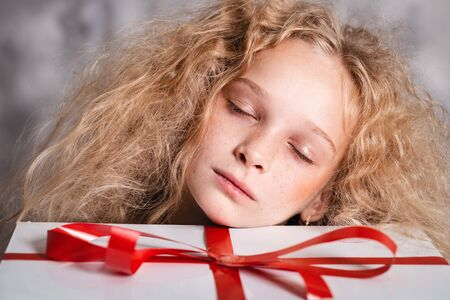 Merry Christmas and happy new year! happy girl with big present in hands closed eyes dreaming about something. Close portrait