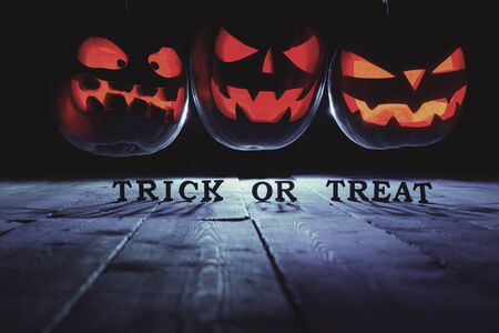 The concept of Halloween. Three glowing fiery light of evil scary pumpkins flying through the air. jack lantern, with the inscription trick or treat, with blue cool light behind on wooden background