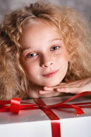 Merry Christmas and happy new year! happy girl with big present in hands looking in camera and smiling. Close portrait Banco de Imagens