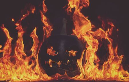 The concept of Halloween. The evil terrible pumpkin is burning in the hellish tongues of flame. Jack Lantern in the middle of the fire