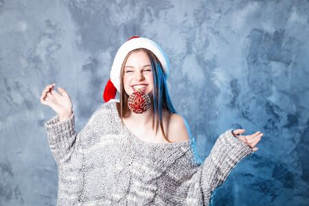 Merry Christmas and happy new year! Adorable happy girl with ball toy in mouth looks very puzzled. Close portrait on gray background. Girl in santa hat and sweater Banco de Imagens