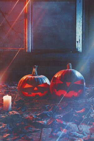 The concept of Halloween. Two luminous evil scary pumpkins, jack-lantern, with candles, leaves and eerie branches outside the window with a warm and cold blue light on the wooden floor in the smoke Banco de Imagens