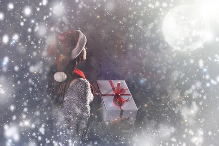 Merry Christmas and happy new year! Adorable female hold present in hands. Close portrait on gray background. Girl in santa hat and sweater look on moonlight under snow falling in night