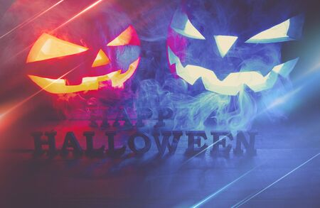 The concept of Halloween. two glowing oranjous and blue light angry scary pumpkin with smoke, jack-lantern, with an inscription of a happy Halloween, on a wooden background Banco de Imagens