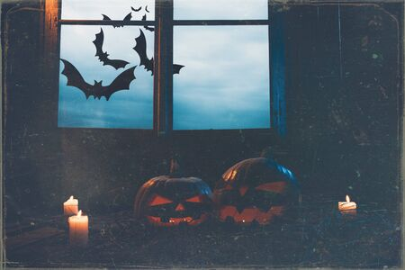 Halloween - pumpkins and candles in an abandoned wooden house on leaves and wooden boards with a warm and cold glow, against the background of a window with a mystic sky and bats