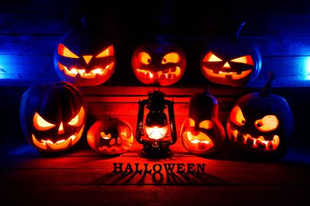The concept of Halloween. Many Evil Scary Pumpkins in the dark with a blue ice glow. Jack Lantern in the middle of the darkness with a lamp bat with Halloween inscription