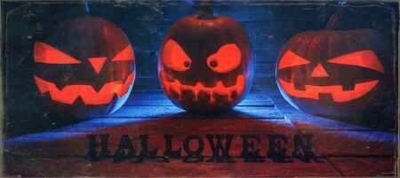 The concept of Halloween. Three glowing with fiery light of evil terrible pumpkins. Jack Lantern, with Halloween inscription, with a blue cold light behind on a wooden background with smoke Banco de Imagens
