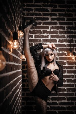 Girl in net tights and a leather jacket with long legs in the interior loft studio. Girl in a bra in high heels. Fashionable Female stands against the wall with her leg up. Fashionable female with white hair