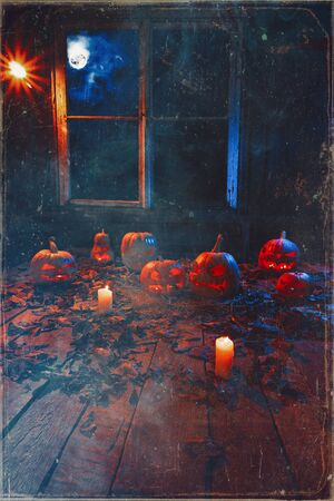 The concept of Halloween. A lot of luminous evil scary pumpkins, jack lantern, with candles, leaves and clouds and a moon outside the window with a warm and cold blue light on the wooden floor in the smoke Imagens
