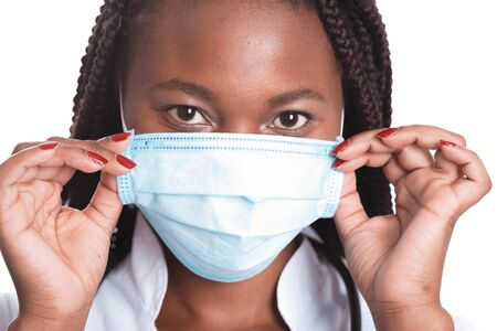Female american african doctor, nurse woman wearing medical coat with stethoscope and mask. Happy excited for success medical worker posing on light background Banco de Imagens