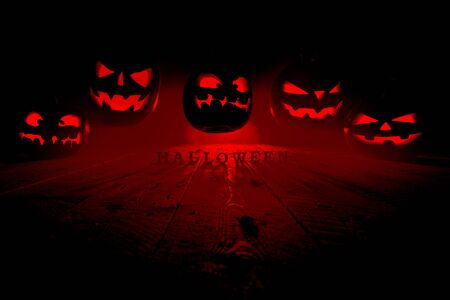 Halloween concept. Many glowing fiery light angry scary pumpkins flying through the air. Jack Lantern, with Halloween inscription, with a blue cool light behind on a wooden background in fog with smoke