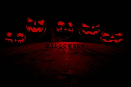 The concept of Halloween. Many Evil scary pumpkins flying in the dark with a blue ice glow. Jack Lantern in the middle of the darkness with an inscription of Halloween and smoke